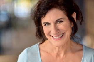 A headshot of Ellen Mittenthal smiling at the camera. She is wearing a light blue shirt.