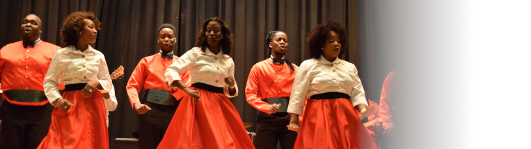 Three Black women in white button ups and orange circle skirts and three black men in orange shirts with black bowties sing in front of a black curtain.