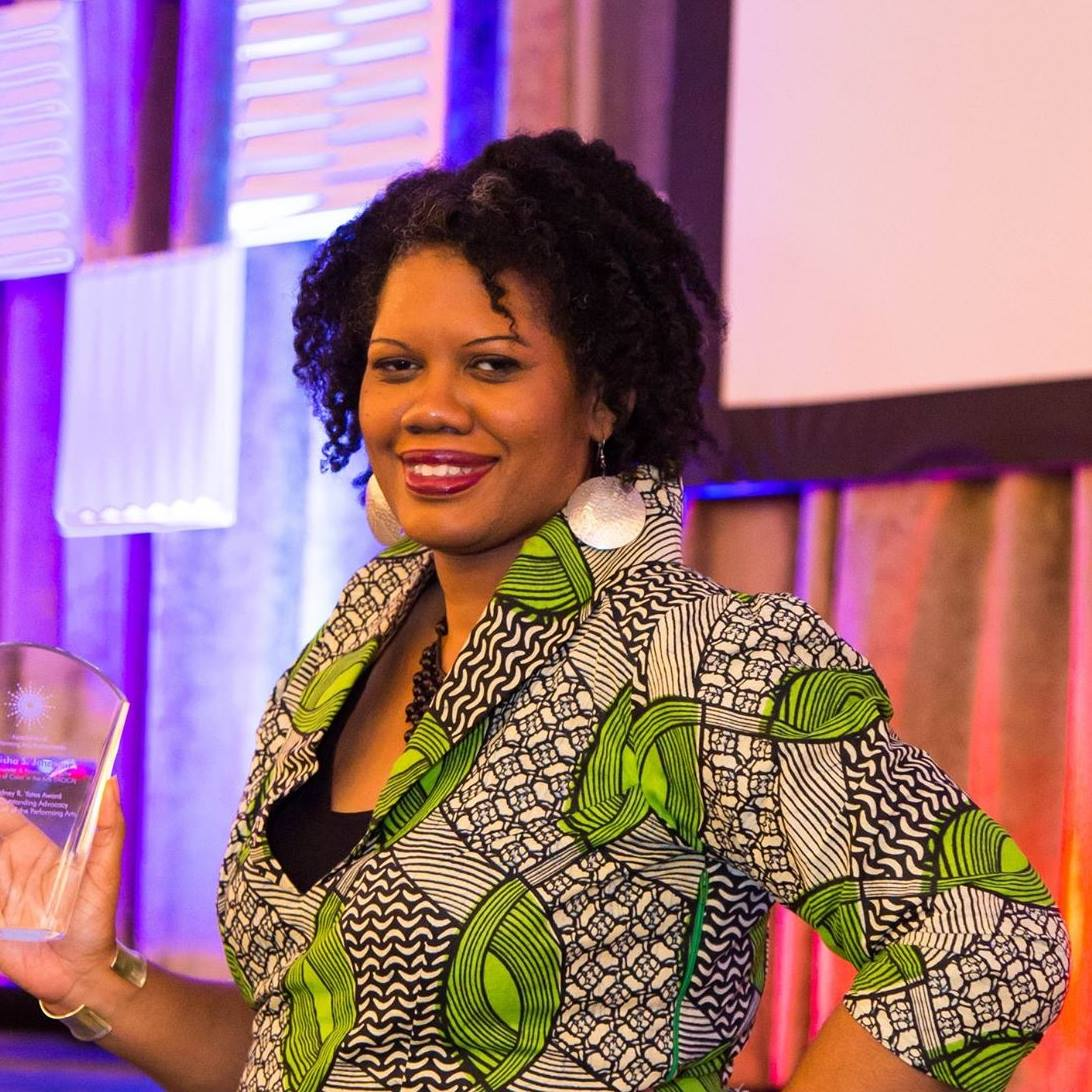 Kaisha Johnson holding an award and smiling at the camera. She is wearing a green, black, and white patterned blouse.
