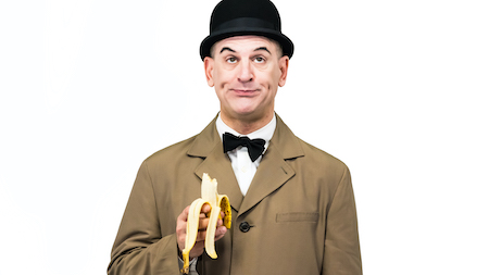 A man wearing a bowler hat, trench coat, and bowtie holds a half-eaten banana with a goofy expression.